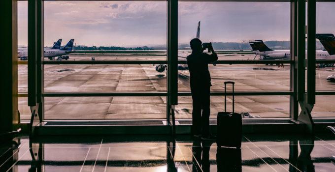 Homem em aeroporto, pronto para viajar de avião